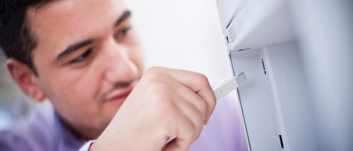 A man inserting a network cable into an ethernet port on the back of a printer