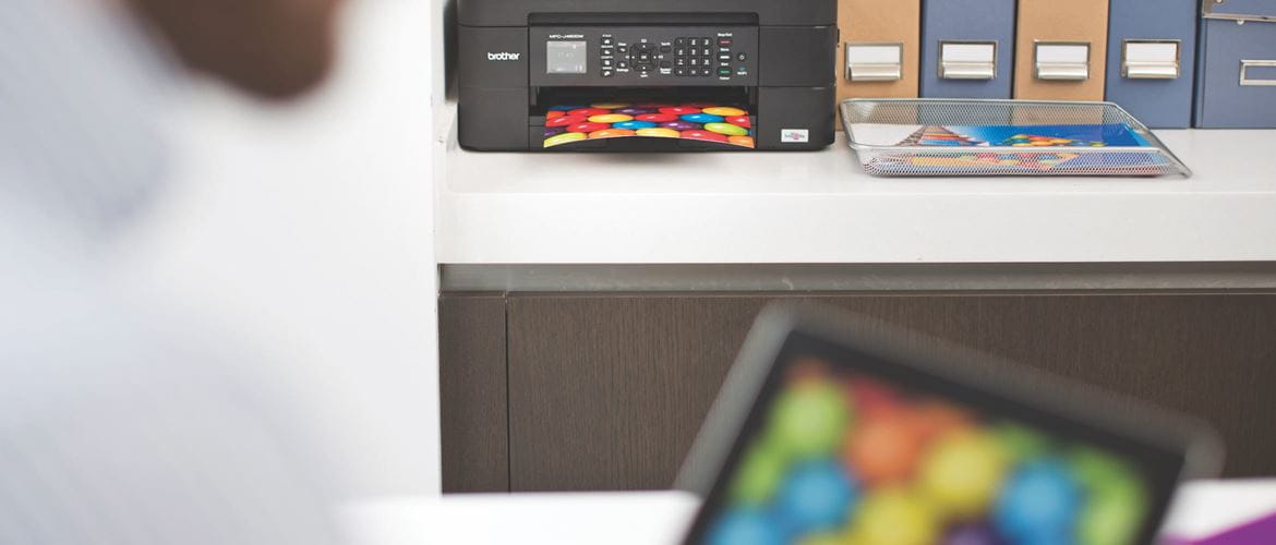 A person wirelessly printing a colourful image from an iPad to a Brother inkjet printer