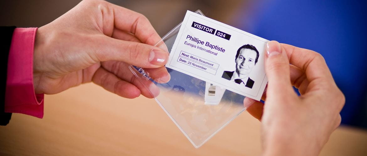 Close-up of a woman inserting a visitor ID printout into a clear clip-on badge