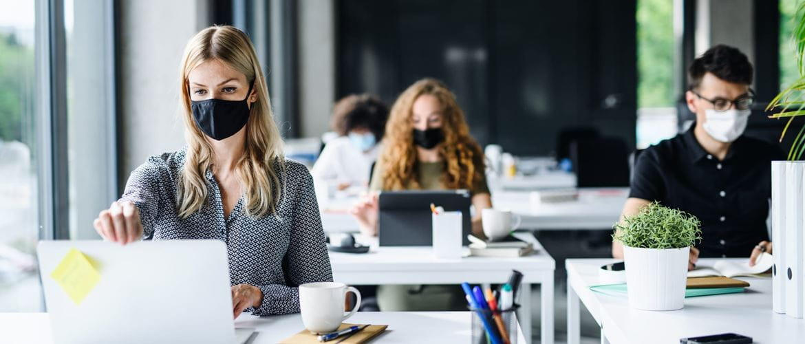 Four colleagues in an office environment working at desks that are spaced apart while wearing face masks to comply with covid-19 guidelines