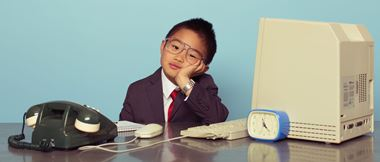 young boy businessman sits behind desk with retro technology on it