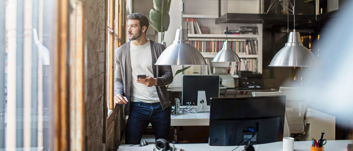 Small medium business employee uses smartphone in modern office setting