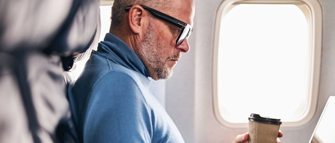 Man on an aeroplane who is working on his laptop whilst drinking a coffee