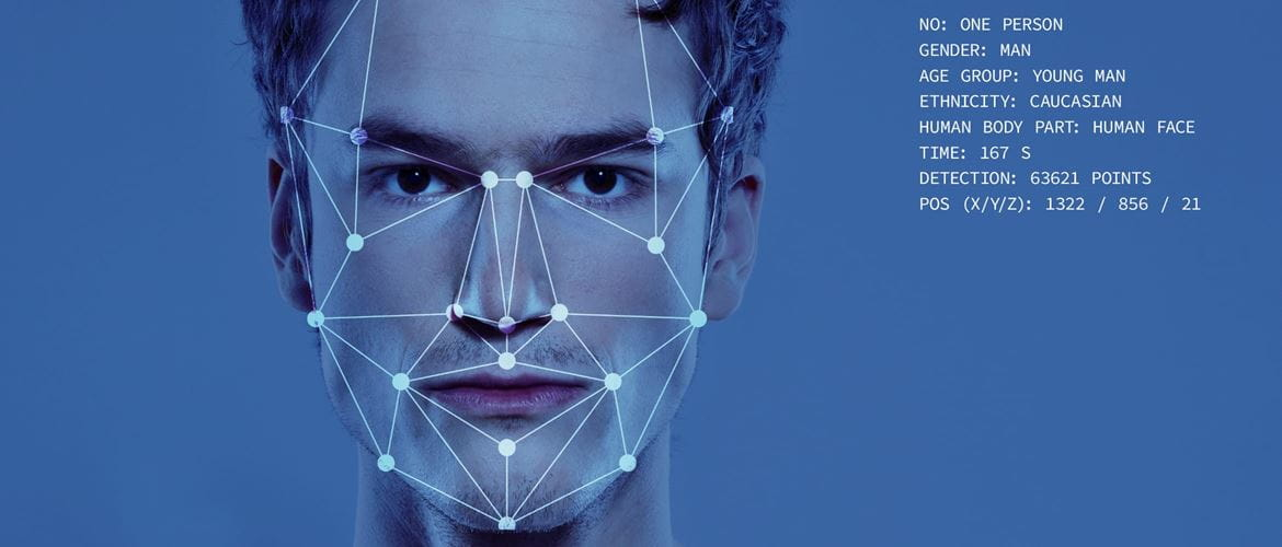 Facial recognition graphical outline superimposed onto a young mans face with his statistics displayed on a blue background
