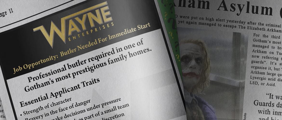 Gotham Globe newspaper opened, showing Wayne Enterprises advertisement for a professional butler and an article about the Joker
