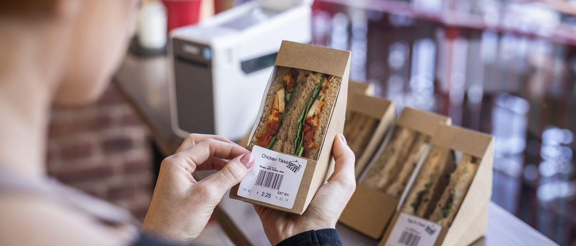 A caterer applying a label to sandwich packaging which includes information about food allergy ingredients