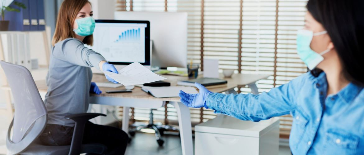 Business woman sat at desk, passing document to female colleague while wearing face covering and surgical gloves in a post-lockdown office environment