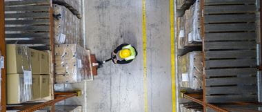 A warehouse worker in a hard hat loading up some boxes