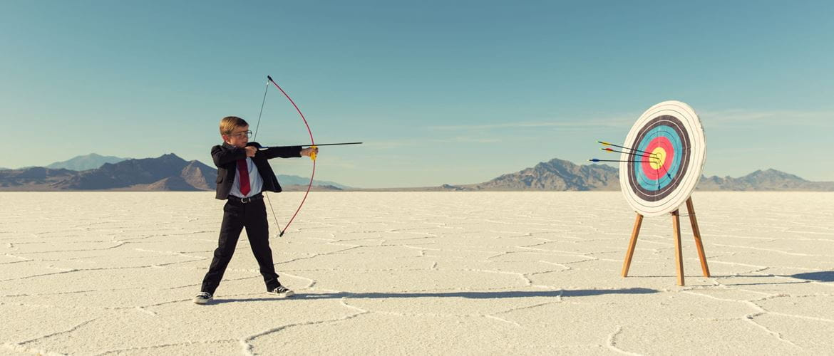 Young boy in a suit takes aim at a target with a bow and arrow