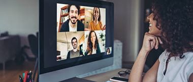 A woman having a video conference with four colleagues on a desktop computer in a home office environment