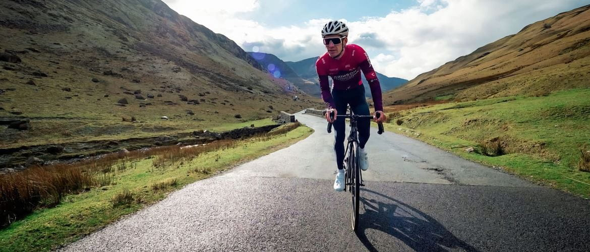 Cyclist Joey Walker riding towards the camera, along an unmarked road  with mountainous terrain to the sides and in the background
