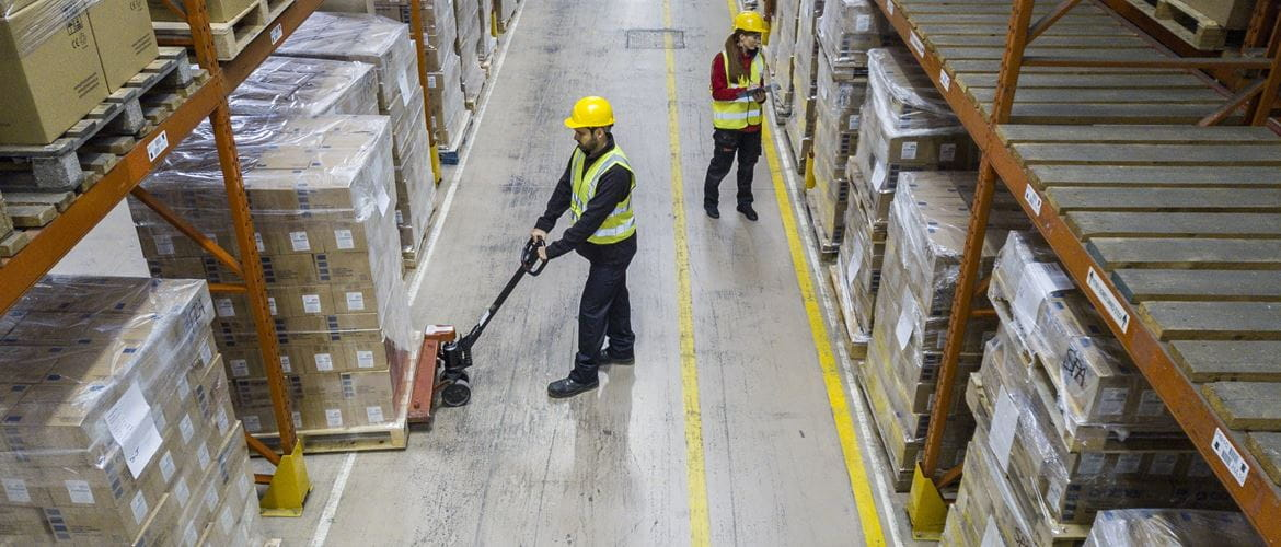 Two warehouse workers inspecting and moving shrink wrapped stock on palettes while wearing hard hats and high vis clothing