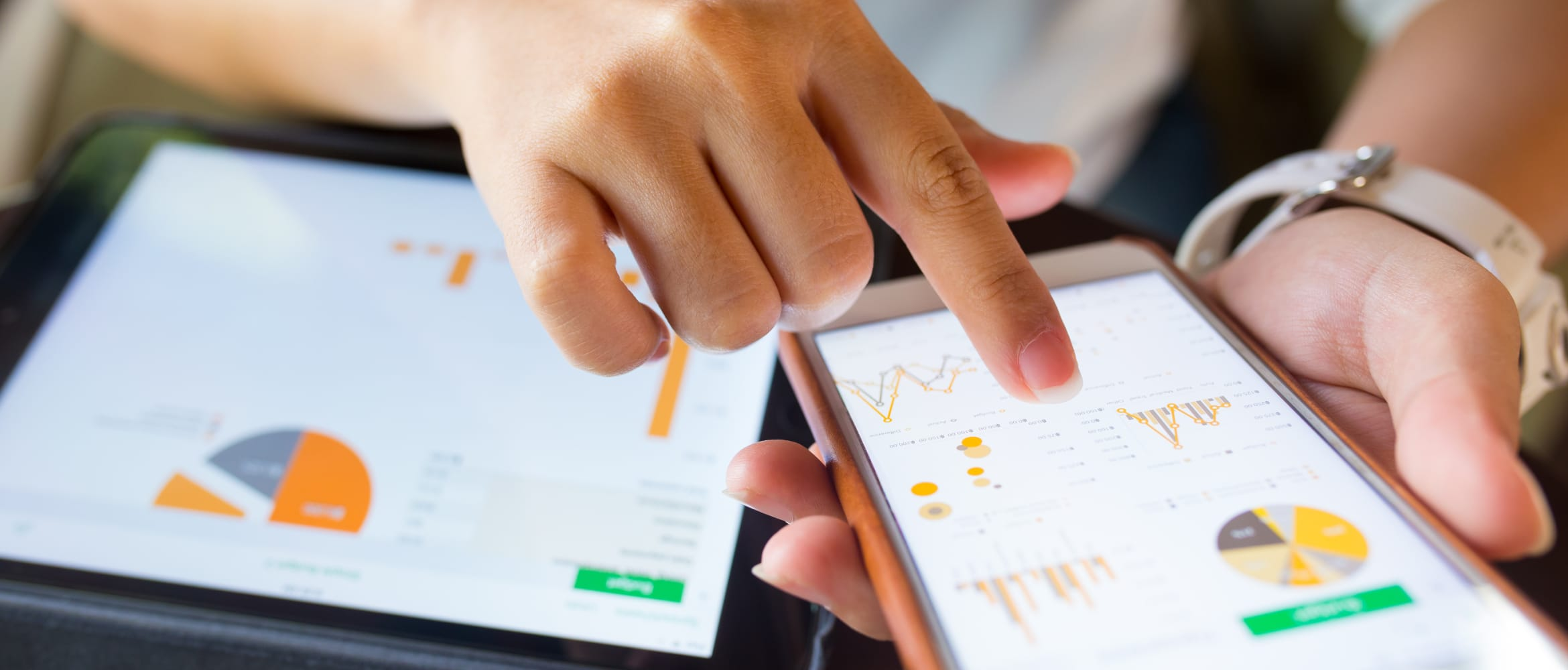 Businesswoman checking data on smartphone and tablet device