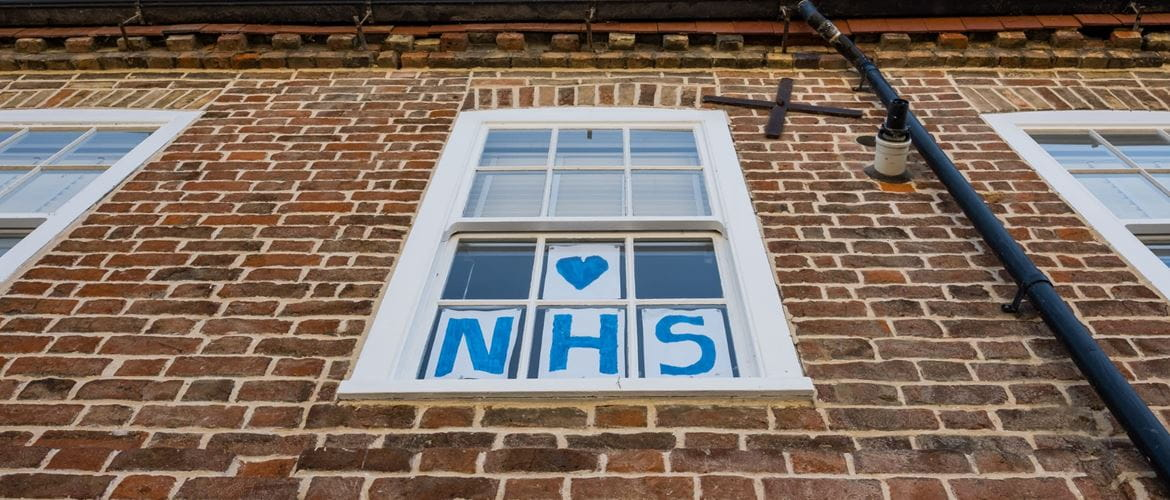 Vertical view of a home-made Love NHS sign attached to a sash window of a town house