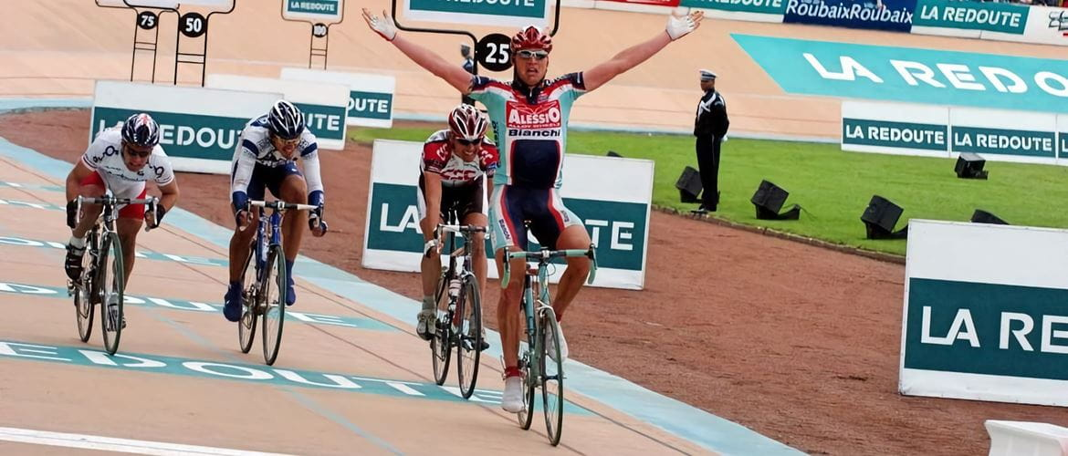 Cyclist Magnus Backstedt crossing the finish line with his arms in the air at Paris-Roubaix