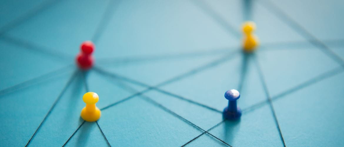 Red, yellow and blue pins on a light blue board, connected by black threat to represent a network