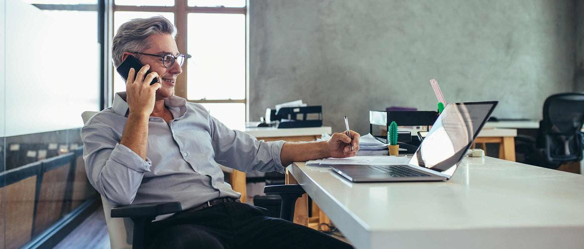 IT manager sitting at desk in front of laptop