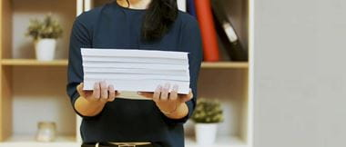 A woman holding a stack of papers with home office shelving in the background