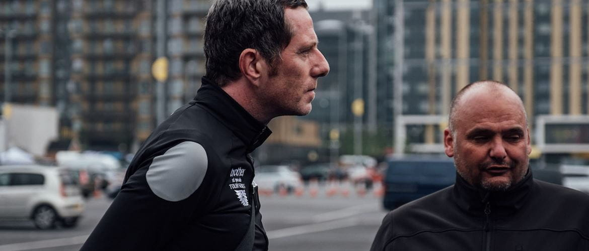 Side profile of Phil Jones MBE, stood next to Simon Howes on a city street with vehicles and tall buildings in the background