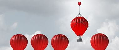 one red hot air balloons flying higher than four other identical balloons
