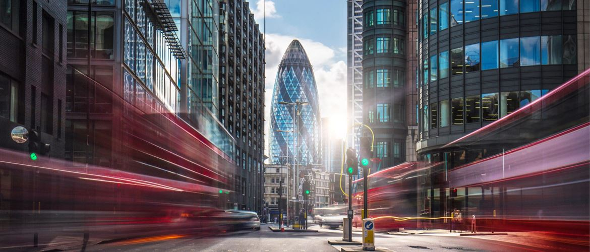 Long exposure shot, blurring red buses as they pass on both sides of a road in London's financial district