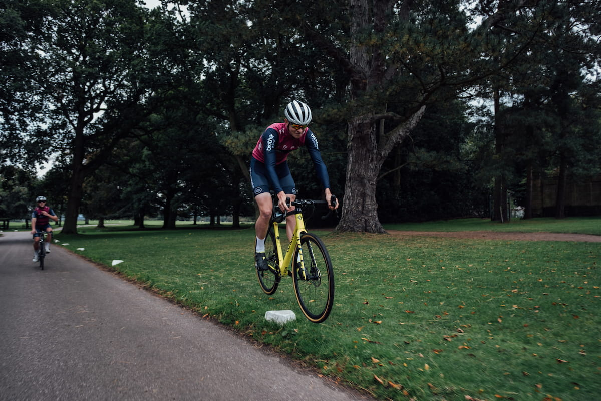 Racing cyclist, purple and blue jersey, blue shorts, white helmet, sunglasses, white socks, black shoes, jumping yellow bike over stone
