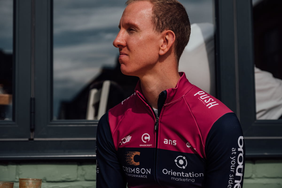 Racing cyclist, male, purple and blue jersey, seated, profile view