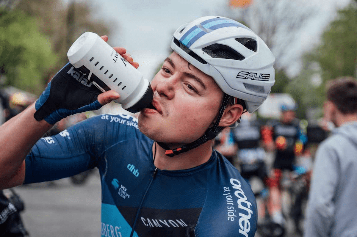 Racing cyclist, male, blue jersey, white helmet, drinking from white bottle
