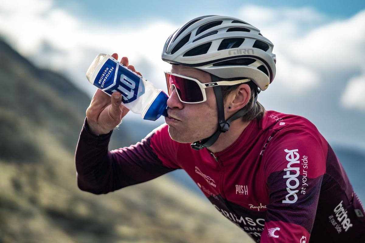 Cyclist Joey Walker rehydrating with greenery and a cloudy sky in the background