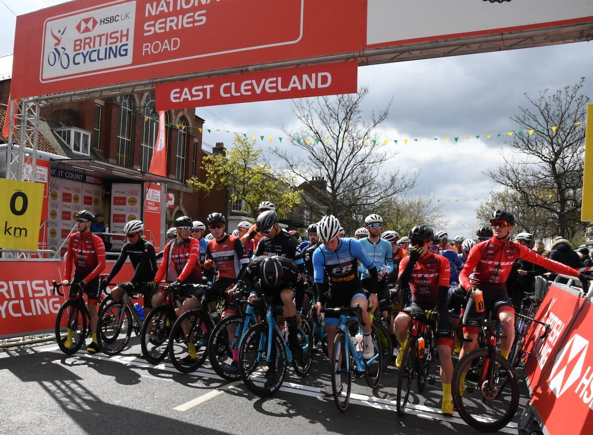 Male racing cyclists, stood with bikes on start line, under start-finish gantry