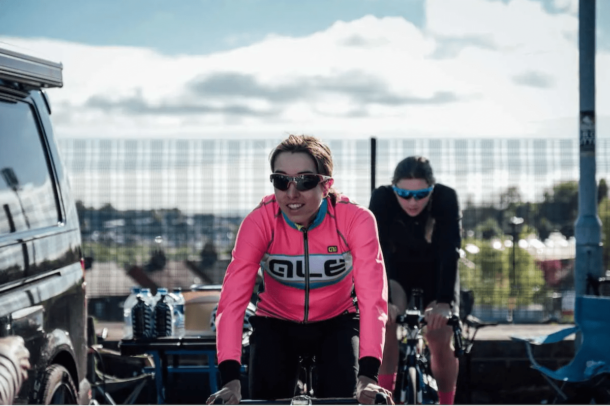 Female racing cyclist, pink jersey, dark hair, dark glasses, smiling