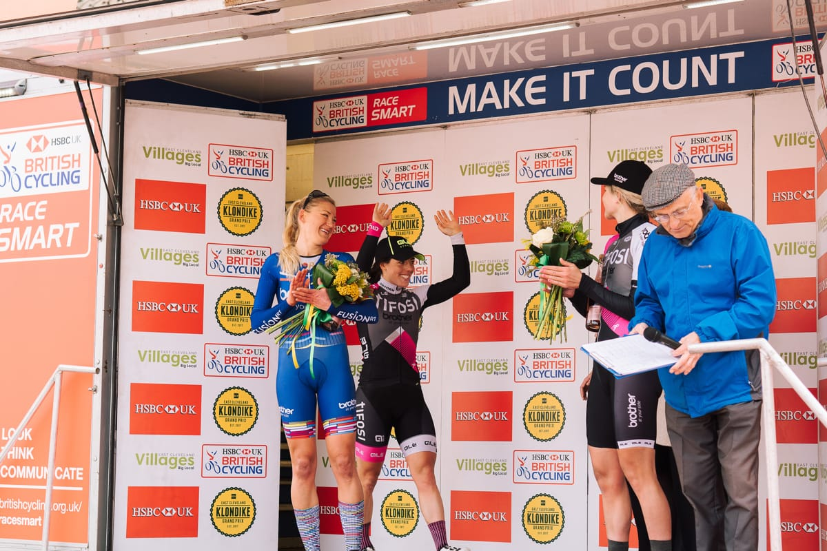 Cyclists Anna Henderson, Rebecca Durrell and Leah Dixon celebrating on a podium after a race