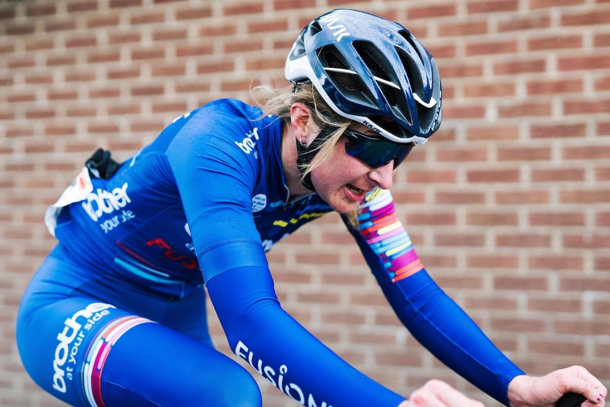 Rebecca Richardson looking determined while cycling past a brick wall