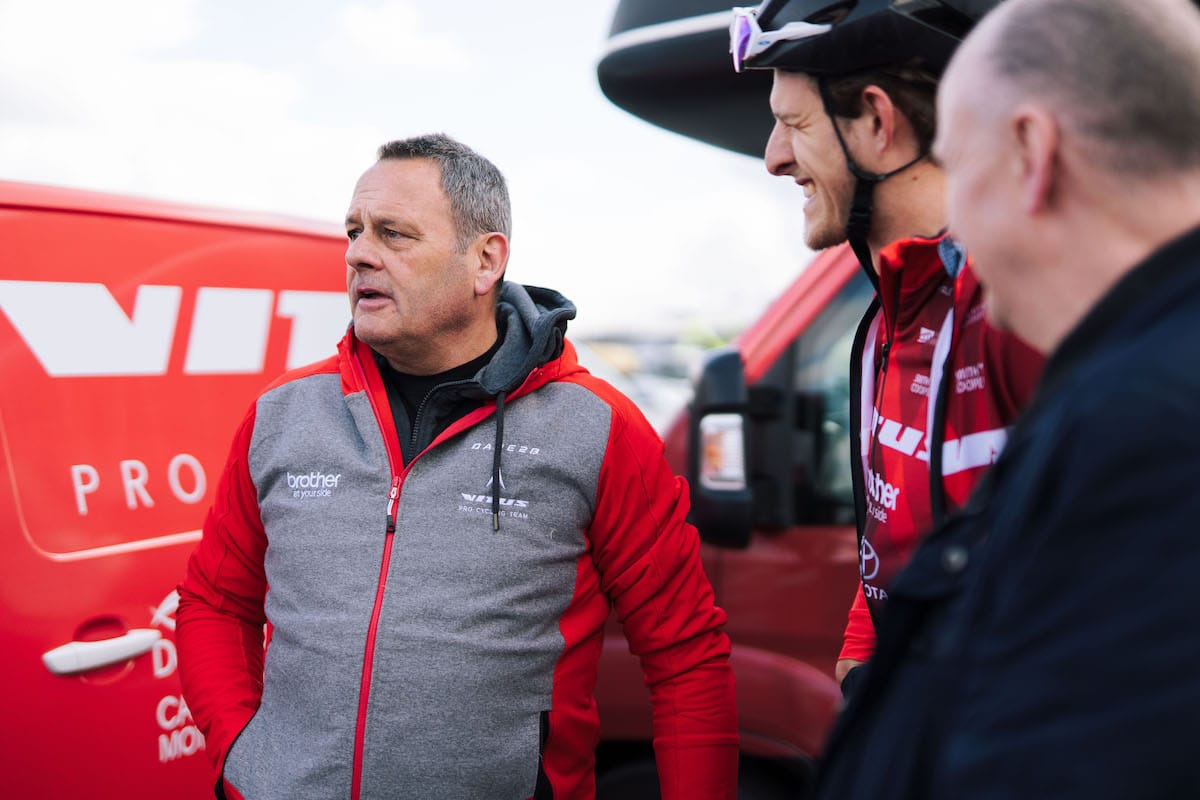 Mick Wright addresses the team in front of a red Vitus Pro Cycling Team van