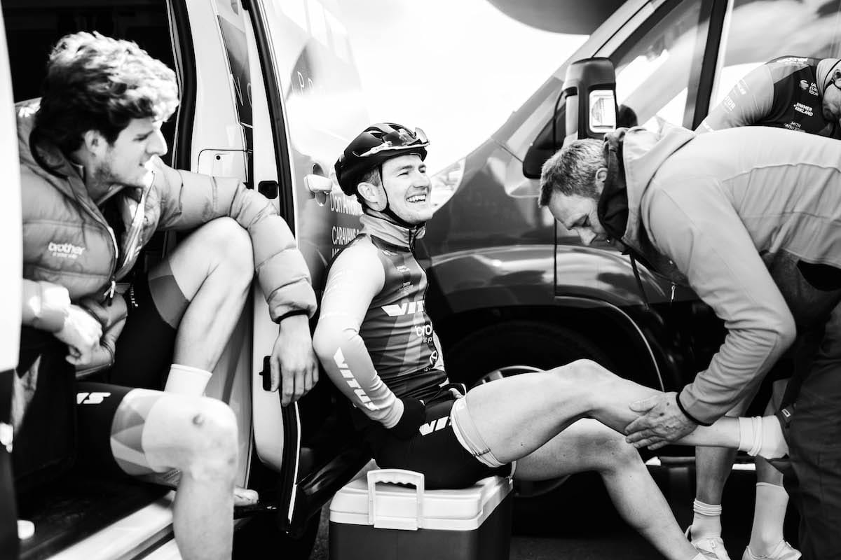 Scott Thwaites receiving a leg massage while sitting on a cool box by a Vitus Pro Cycling Team van