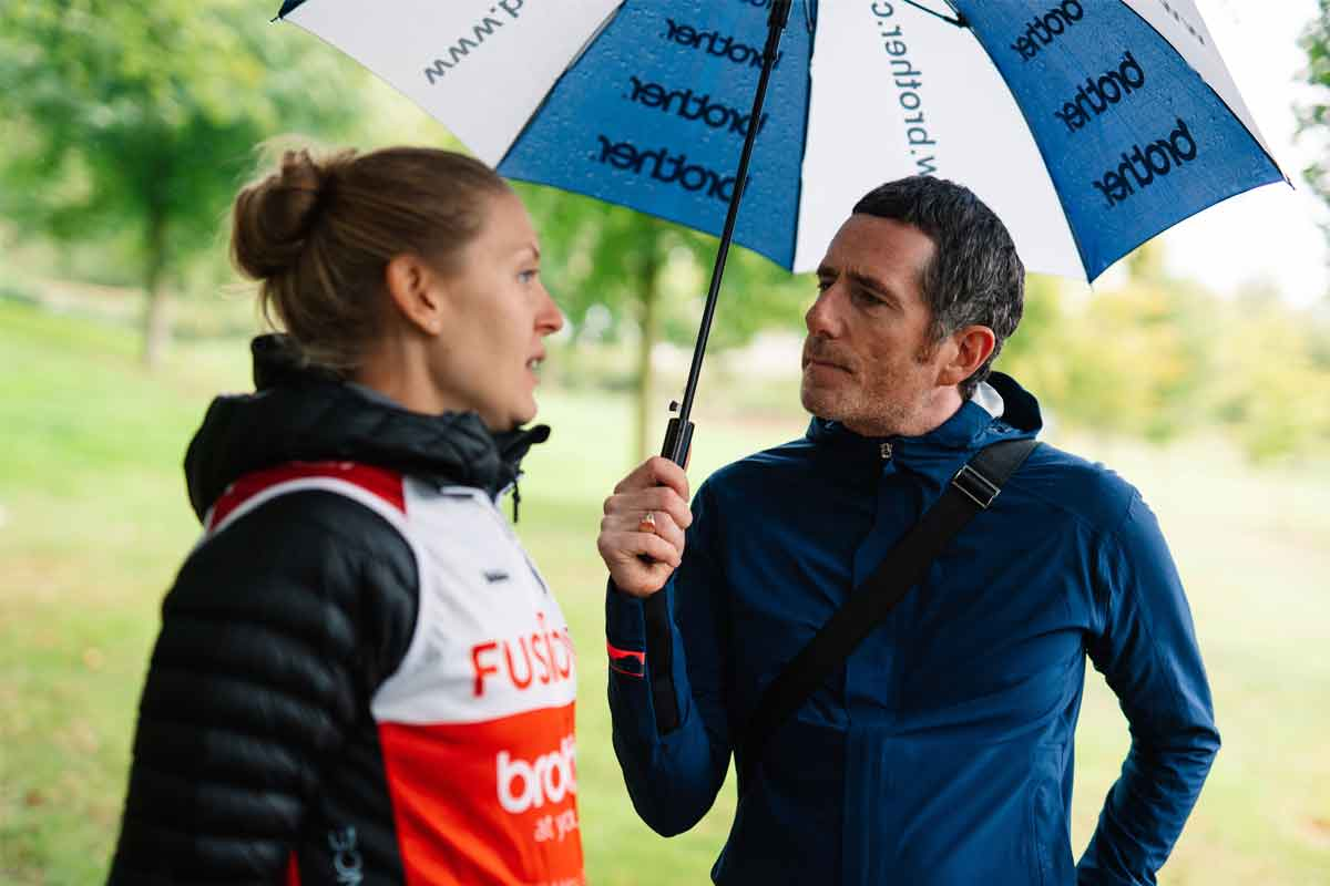 Fusion RT cyclists chatting under an umbrella to Brother UK's Managing Director, Phil Jones
