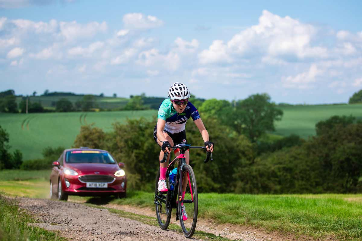 Cyclist Sophie Wright followed by a support car