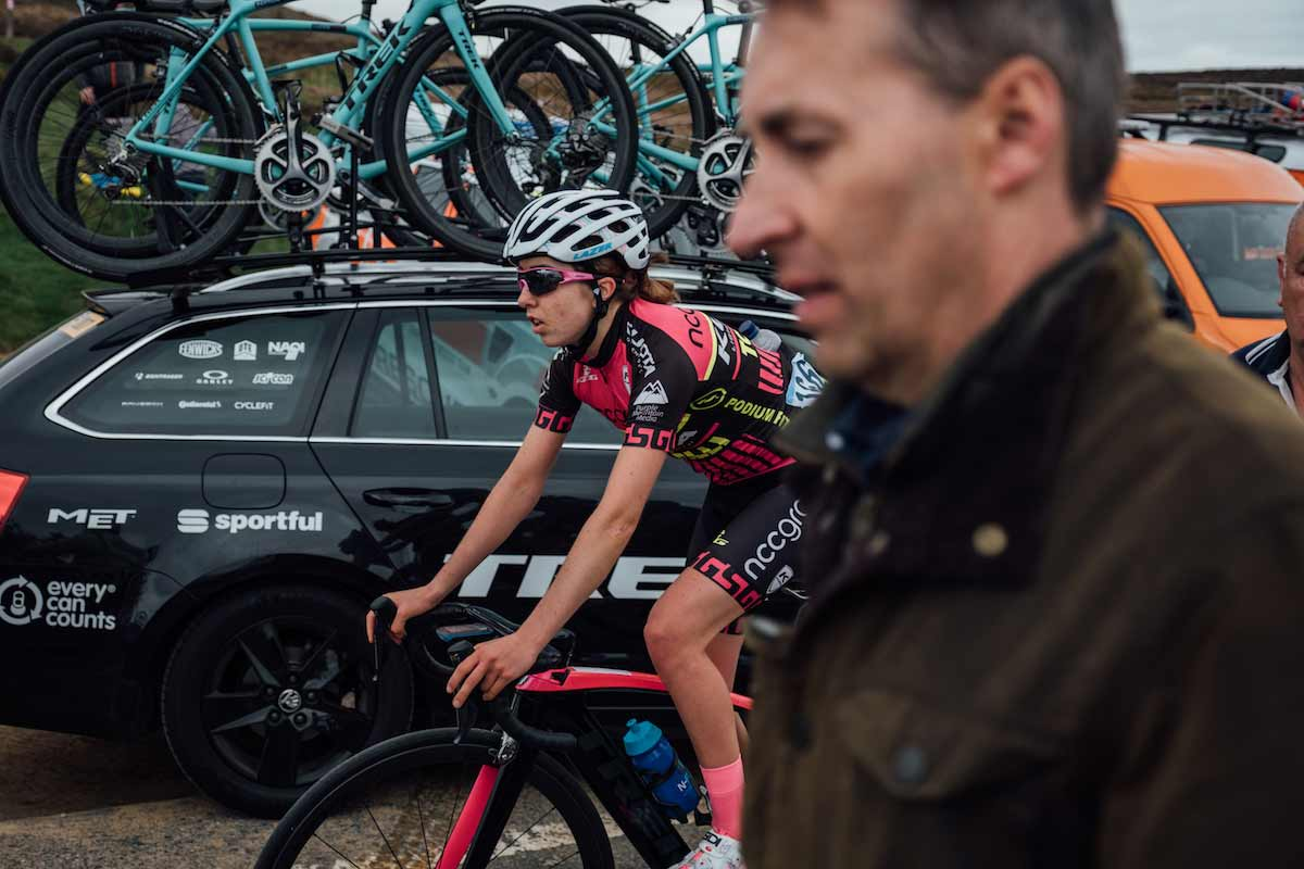 Sophie Wright cycling past a support car