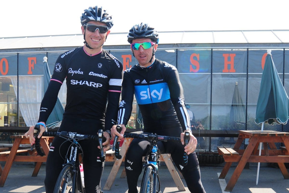 Brothers Dean and Russell Downing wearing cycling clothing while straddling their bikes in front of a glass walled building with tables and parasols in the background