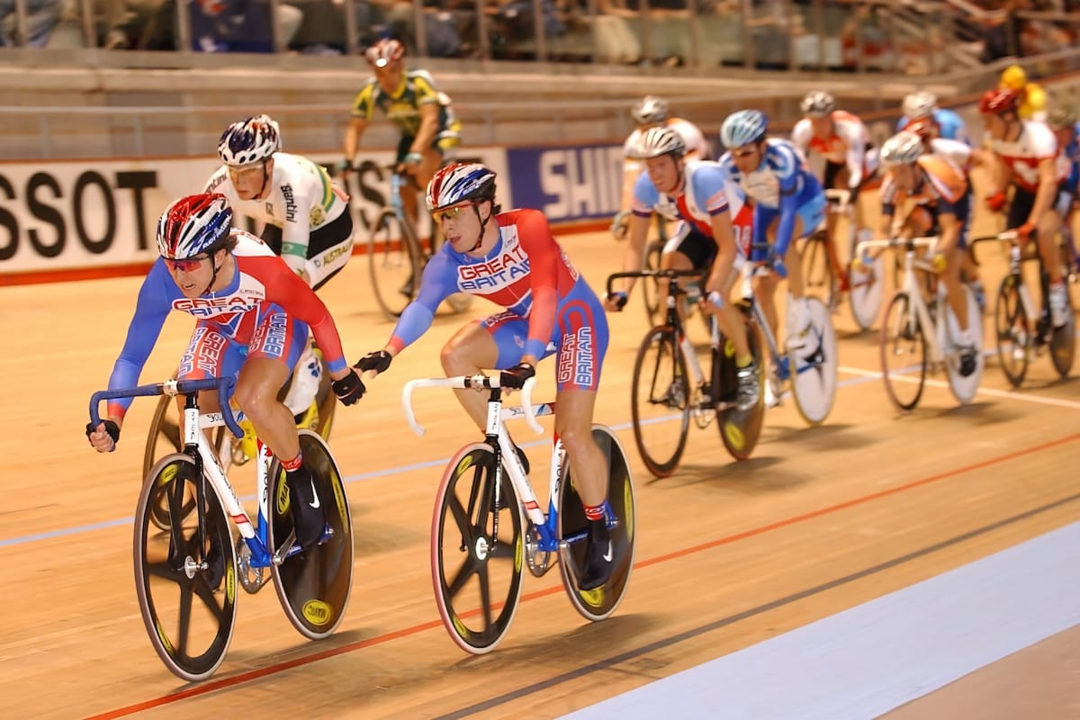 Brothers Dean and Russell Downing leading a group of cyclists at a velodrome with spectators in the background