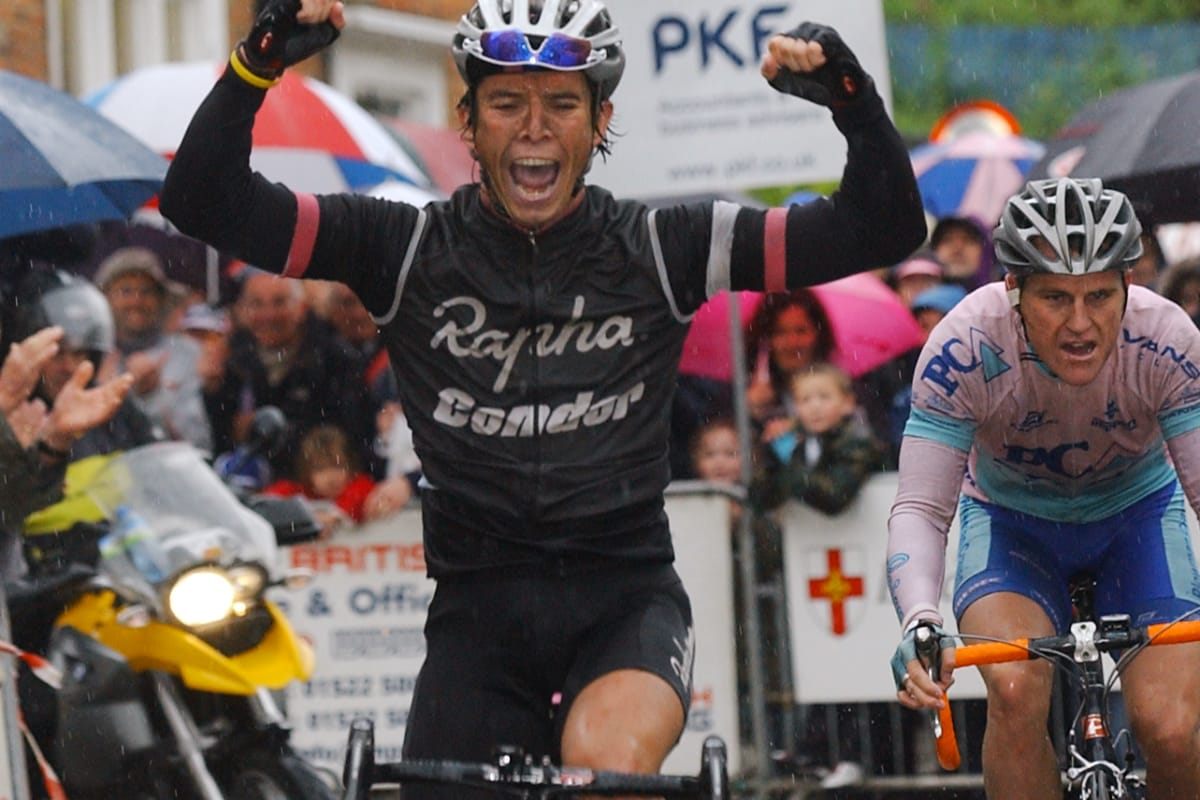 Cyclist Dean Downing with his arms in the air as he crosses the finishing line with spectators and other riders in the background