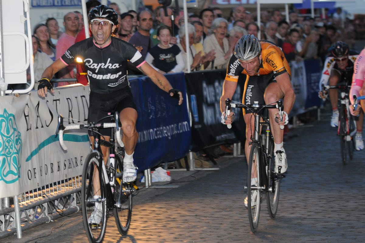 Cyclist Dean Downing crossing the finishing line with another cyclist close behind and spectators cheering behind a barrier