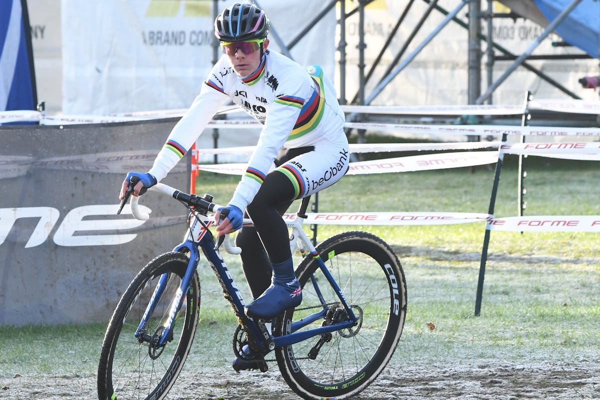 Cyclist  Ben Tulett riding along a muddy field with banners and scaffolding in the background