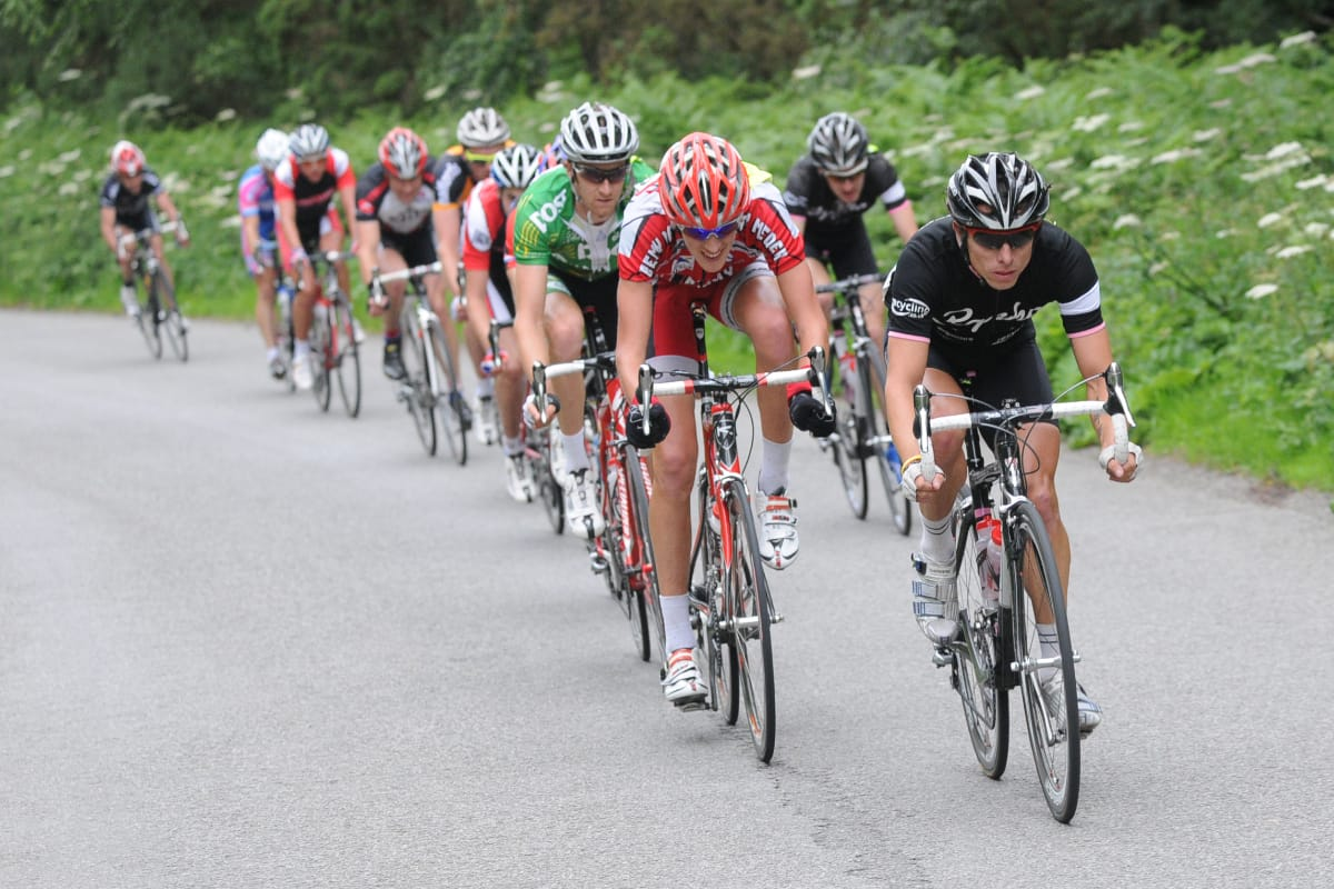Cyclist Dean Downing leading a group of cyclists as they approach the camera while riding up a hill with greenery in the background