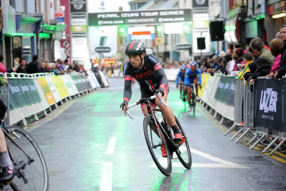 Cyclist Dean Downing taking a bend in the road with spectators behind barriers on either side in a built up area
