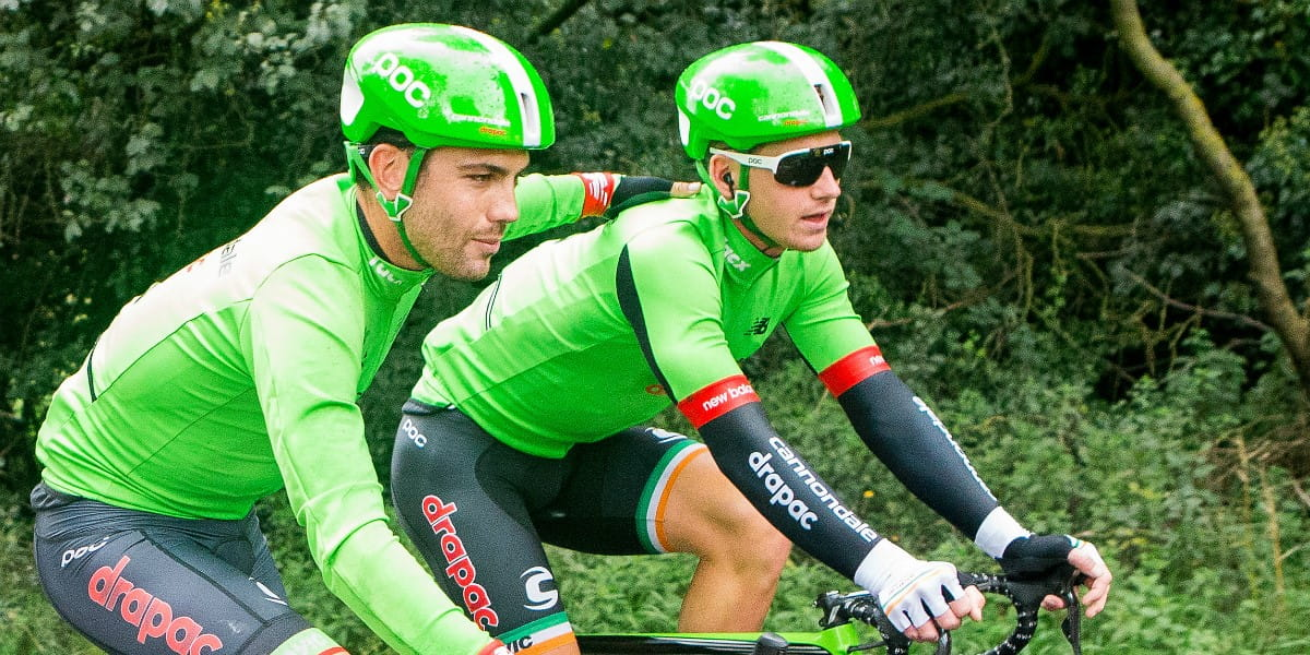 cycling teammates cycle with arms around each other