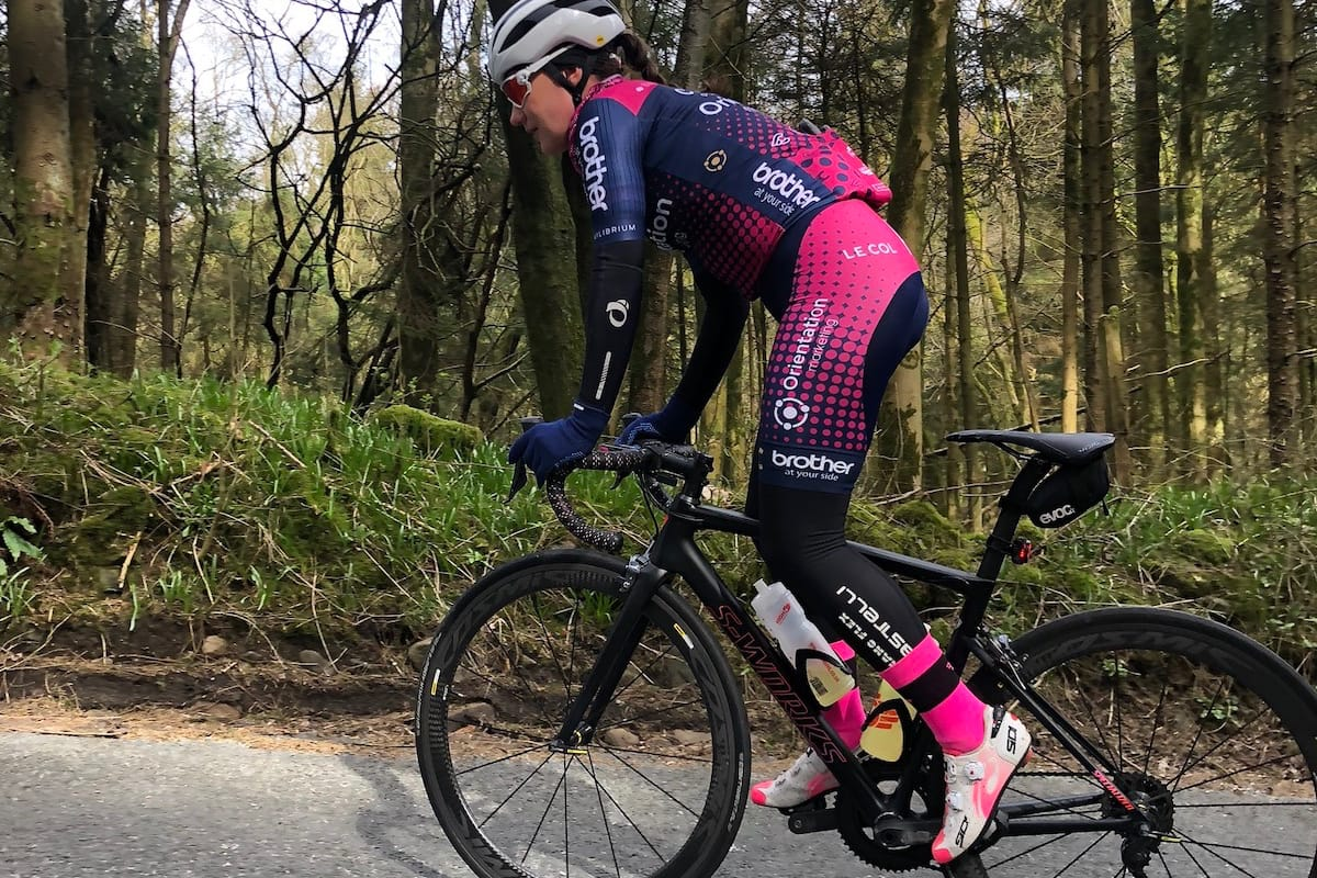 Cyclist Melissa Greaves standing and leaning over the handlebars while riding along a country road with trees and greenery in the background