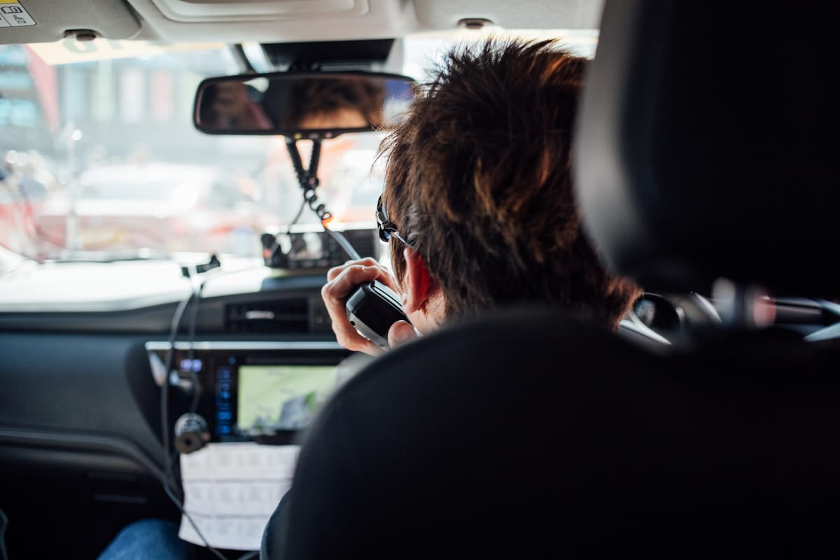 Cherie Pridham talking on a CB radio viewed from the back seat of a cycling team support vehicle