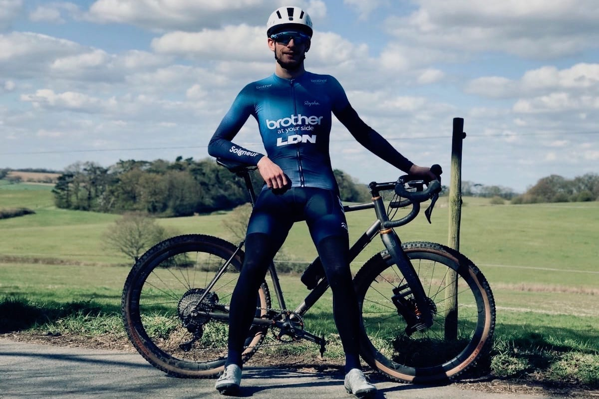 Cyclist Tim Allen standing in front of his bike at the side of a country road with green fields in the background