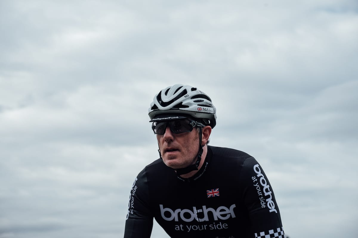 Phil Jones MBE wearing a helmet and Brother cycling team jersey as he rides towards the camera with grey sky in the background
